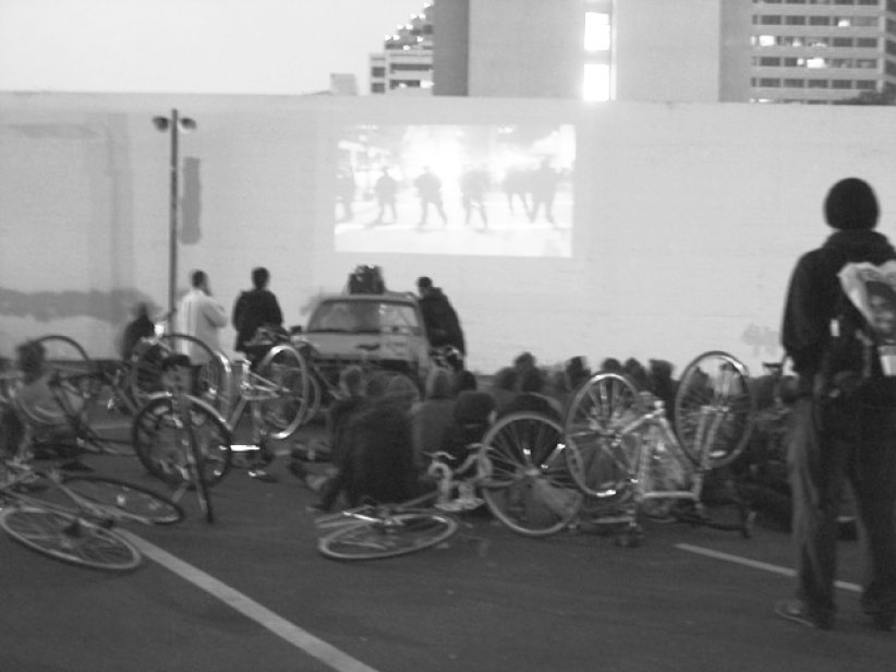 bicyclists sitting in a lot watching film